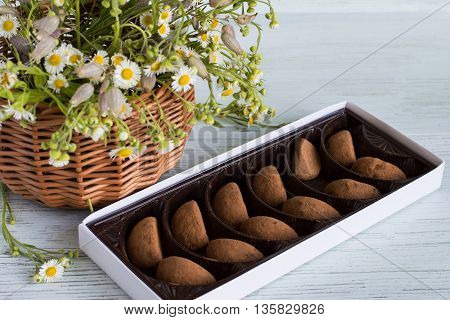A box of chocolates and a basket of flowers on a light wooden background.