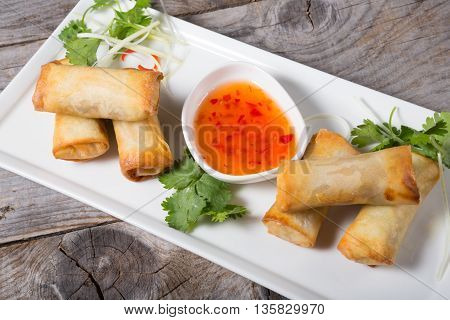 Spring rolls with chili sauce on wooden board