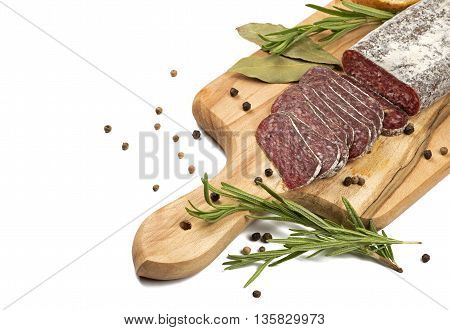 Sliced flat sausage on wooden cutting board