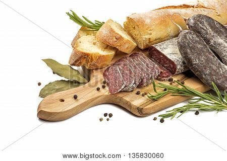 Sliced flat sausage and bread on wooden cutting board