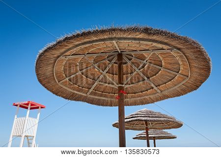 Life guard stand and three beach umbrellas on a blue sky background