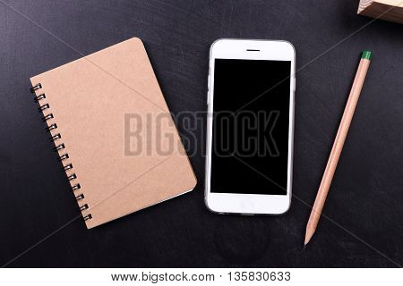 blank screen smartphone with notebook and pencil on black background