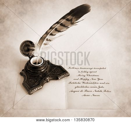 Antique Bronze inkpot with feather and handwritten congratulatory text in four languages to send foreign friends - Sepia toned artwork in retro style