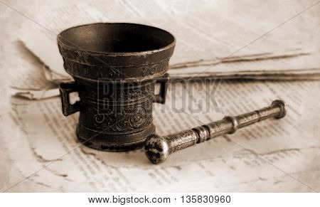 Old bronze mortar and pestle on the pages of ancient book with effect of shallow depth of field and vignette - Sepia toned artwork in retro style