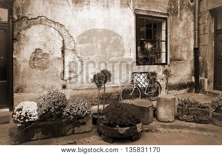Picturesque wall of an old house in the evening time - Sepia toned artwork in retro style