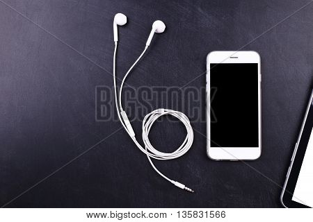 blank screen white color smartphon with earphone