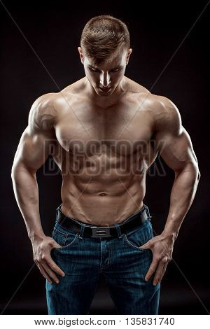 Muscular bodybuilder guy doing posing over black background. Naked torso in jeans.
