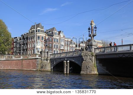 AMSTERDAM, NETHERLANDS - MAY 6, 2016: Beautiful The Blue Bridge (Blauwbrug) is a bridge over the Amstel River which connects the Rembrandtplein area with the Waterlooplein, Amsterdam, Netherlands.