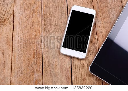 blank screen smartphone and tablet on wooden background