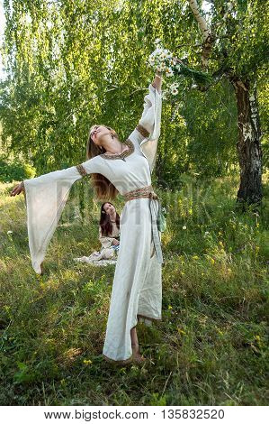 Two attractive women in traditional russian clothes relaxes over nature background. Ivan Kupala Holiday Celebration