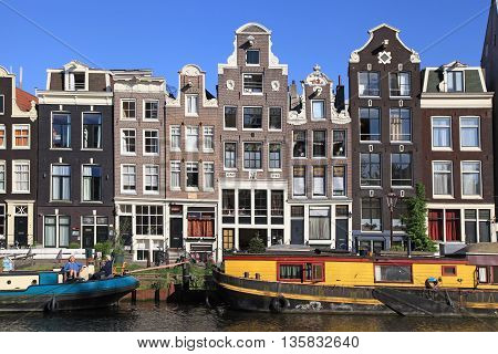 AMSTERDAM, NETHERLANDS - MAY 8, 2016: Old houses of traditional architecture and houseboats along canal in Jordan neighborhood, Amsterdam, Netherlands. Amsterdam is capital and most populous city of Netherlands