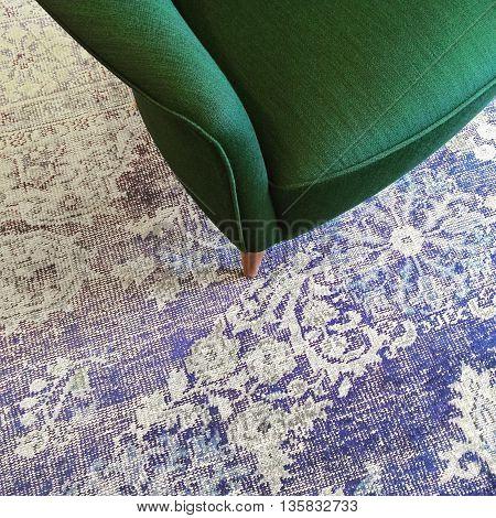 Green armchair on blue retro style carpet. Stylish furniture.