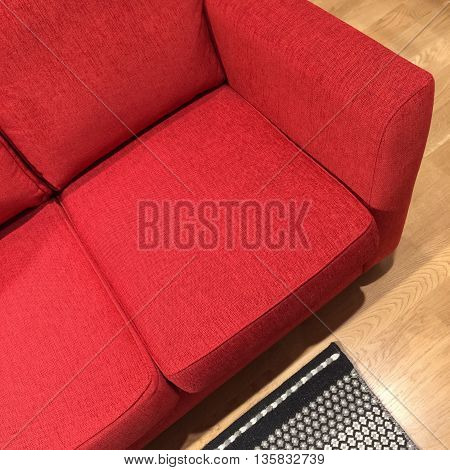 Comfortable classic red sofa on wooden floor.