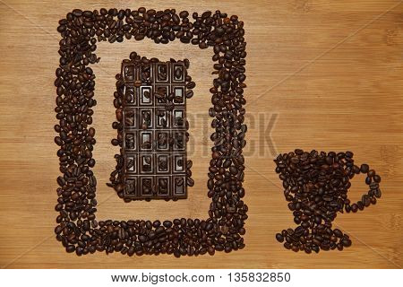 Cup of coffee made from coffee beans with bar of chocolate in frame of coffee seeds. Image of coffee cup with coffee beans on wooden table.