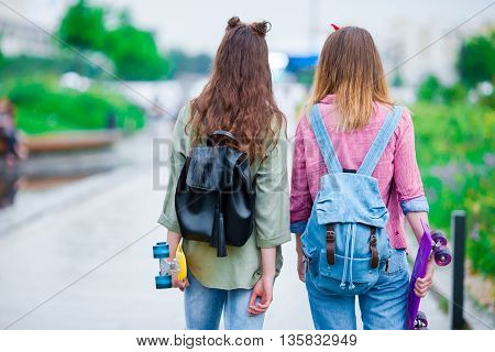 Two hipster cute girls with skate outdoors
