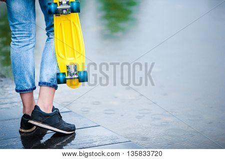 Closeup legs and skateboard in female hands