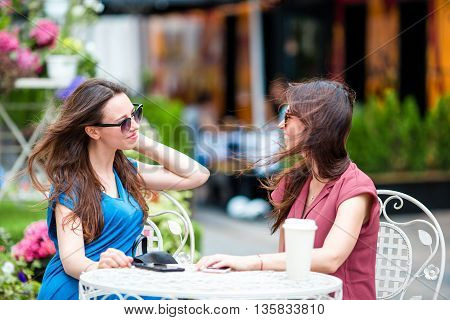 Two nice girl friends sitting in outdoor cafe using smartphone