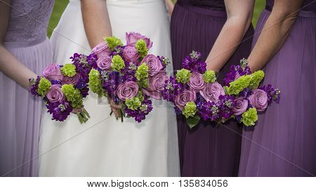 horizontal photograph of a bride and her bridesmaids holding their bouquets together
