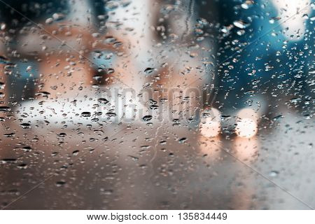 Drops Of Rain On Blue Glass Background. Street Bokeh Lights Out Of Focus. Abstract Backdrop