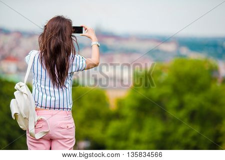 Young caucasian woman making photo by mobile phone from the observation place