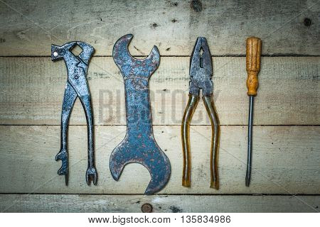 Old tools lie on the boards. Top view of a wrench vernier calipers pincers.
