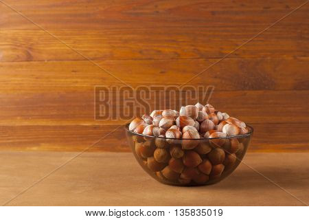 The crude hazelnut in translucent plate on the table with a wooden background. Healthy food.