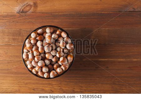 The crude hazelnut in translucent plate on the table with a wooden background with the top view plate Is located on the left in the frame. Healthy food.