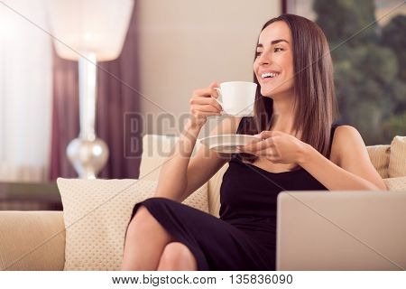 Pleasant meeting. Cheerful contented young businesswoman sitting on the sofa and holding a cup of coffee while looking aside