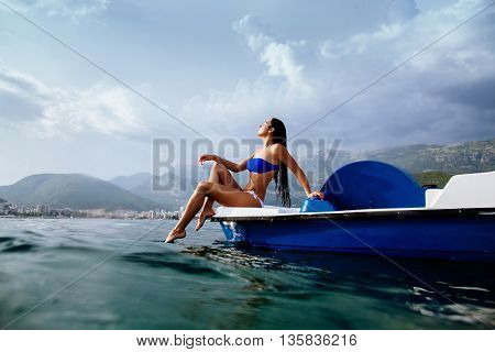 Girl Sunbathe In Sea On Paddle Boat Catamaran