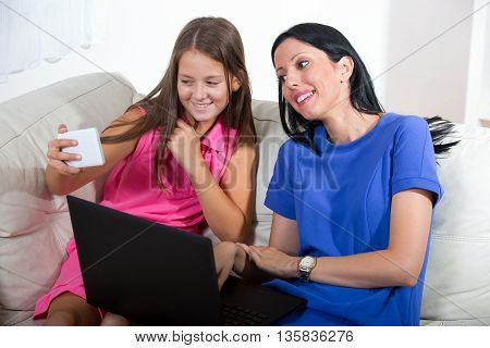 Smiling mother and her daughter using a notebook and smartphone