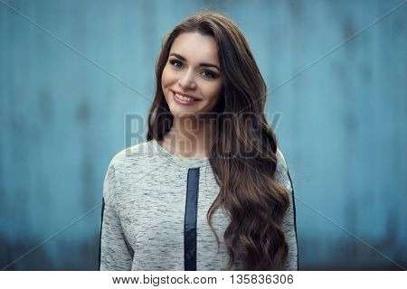 Happy attractive smiling girl portrait against blue old wooden wall. Pretty stylish fashionable woman in gray hoodie with long curly hair looking at you. Shallow DOF, blurred background