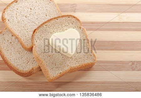 Healthy eating concept - piece of wheat bread with a heart shaped symbol of butter