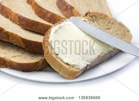 Close up a knife spreading butter on bread.