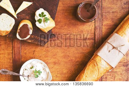 Appetizer set with freshly baked French baguette, chocolate ganache and savory cream on a table