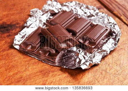 Broken chocolate bar on foil on a dark wooden table