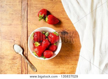 Fresh and ripe strawberries in a bowl with sugar on a wooden table
