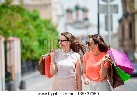Two girls shopping in the city walking with their purchase