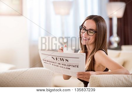 What is new. Amazing relaxed smiling woman sitting on the couch with a cup and reading newspaper