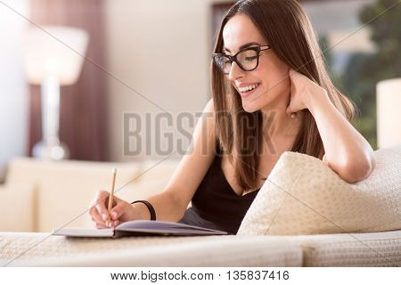 I am happy. Young delighted woman taking notes in a notebook while sitting on the sofa and touching a neck with her hand
