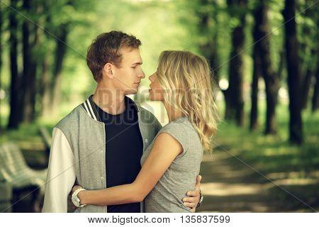 Happy young couple. Beautiful smiling blonde girl hugging her boyfriend