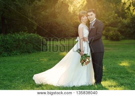 Beautiful just married couple standing and posing in park at sunset. Soft lovely light. Bride in long white dress with flying hem