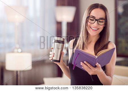 All is planned. Happy beautiful young businesswoman looking at her notebook while standing and holding a thermo mug
