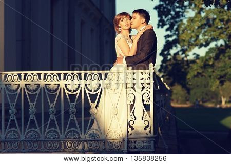Beautiful just married couple hugging at terracce in park near palace