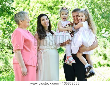 many generations family and pregnant woman in city park, summer season, green grass and trees