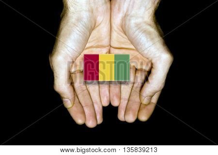 Flag Of Guinea In Hands On Black Background