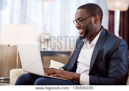 Pleasant work. Profile of an afro American businessman working on the laptop while sitting on the sofa in the hotel