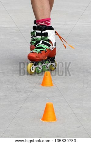 girl crossing while skating with cones in a grey floor