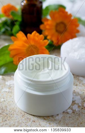 Essential Oil Bottle Calendula Aromatherapy And Salt On Brown Stone Background. Spa Calendula.