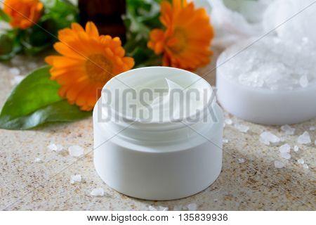 Essential Oil Bottle Calendula Aromatherapy And Salt On Brown Stone Background. Spa Calendula.