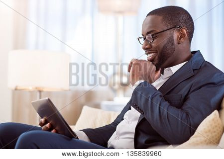 Some relaxation. Handsome confident afro American man using a tablet while sitting on the sofa and touching his chin